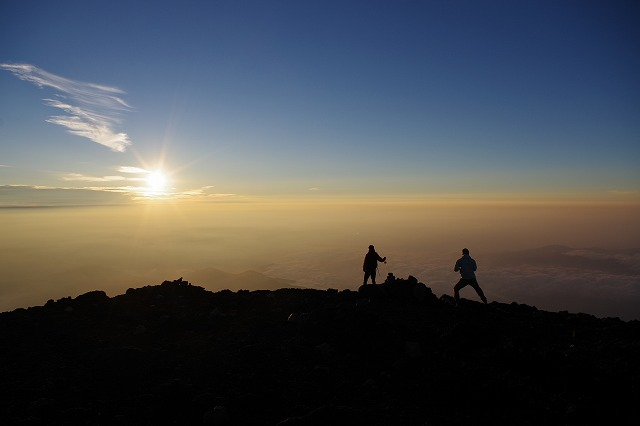 富士山頂上でご来光を背景に記念撮影する登山者